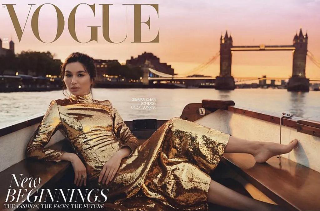 A modelo Gemma Chan sentada em um barco no pôr do sol.